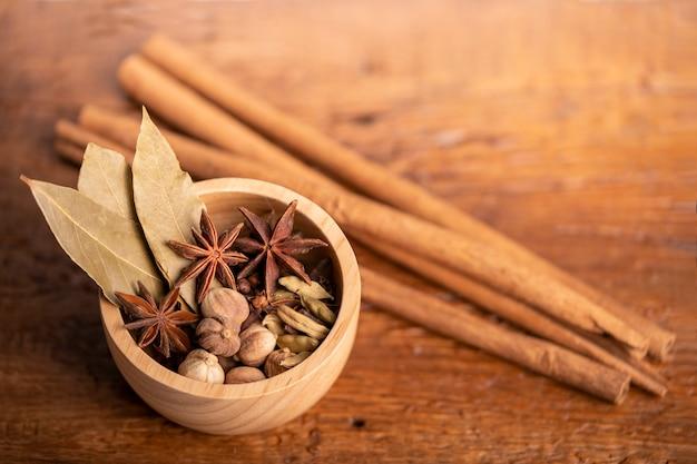 Specerijen en kruiden ingrediënten voor het koken van curry curry poeder kruidnagel kardemom kaneel karwij op houten ondergrond