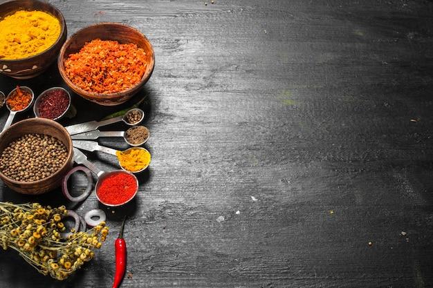 Specerijen en kruiden met maatlepels op zwart bord.