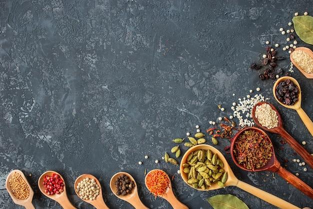 Specerijen en kruiden op zwarte steen, plat leggen.