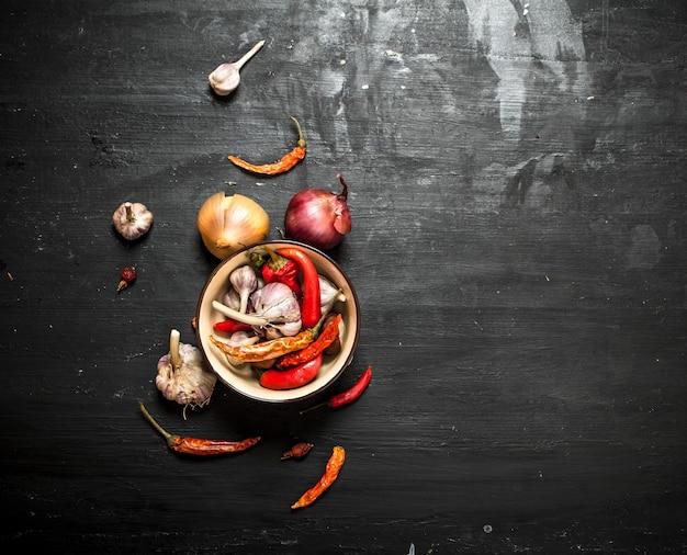 Specerijen en kruiden. verse ui, knoflook en chili. op het zwarte bord.