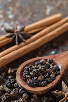 Specerijen en kruiden. voedsel en keukeningrediënten. kaneelstokjes, anijssterren, zwarte peperkorrels en kardemom op een gestructureerd oppervlak.