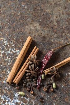 Specerijen en kruiden. voedsel en keukeningrediënten. kaneelstokjes, anijssterren, zwarte peperkorrels, spaanse peper, kardemom en kruidnagel op gestructureerd oppervlak