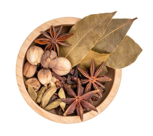 Specerijen en kruideningrediënten voor het koken kerrie in houtslag, kerriepoeder, kruidnagel, kardemom, kaneel, karwij die op witte achtergrond met het knippen van weg wordt geïsoleerd.