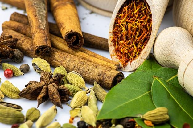 Specerijen en kruiderijen gemorst op een witte tafel, houten lepels door close-up.