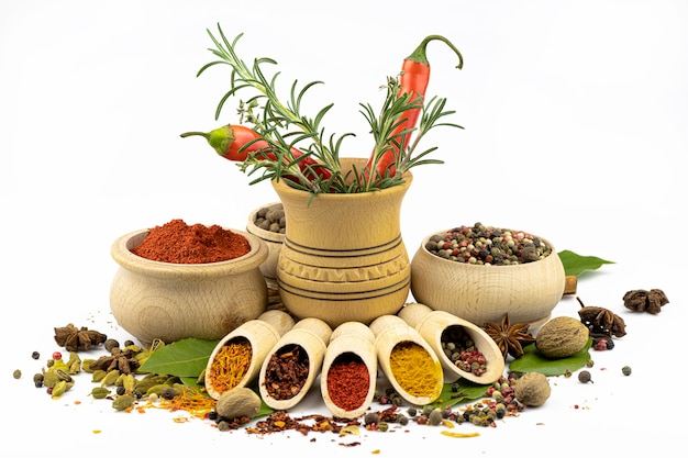 Specerijen en kruiderijen in houten lepels en kommen, scherpe peper en rozemarijn in een vijzel door close-up geïsoleerd op een witte achtergrond