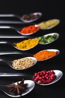 Specerijen en specerijen om te koken op een zwarte achtergrond