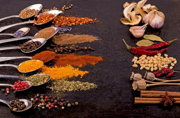 Specerijen en specerijen voor het koken op een zwarte achtergrond.