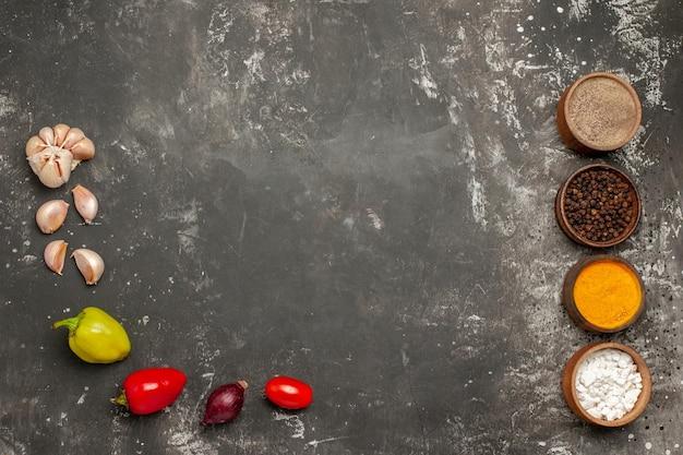 Specerijen paprika knoflook ui tomaten en kommen met kruiden op de donkere tafel
