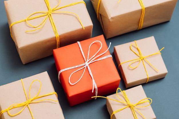 Speciaal cadeau voor een geliefde. vakantiebeloning dankbaarheid en felicitatie concept. rode geschenkdoos die opvalt onder het assortiment van pakketten in kraftpapier.