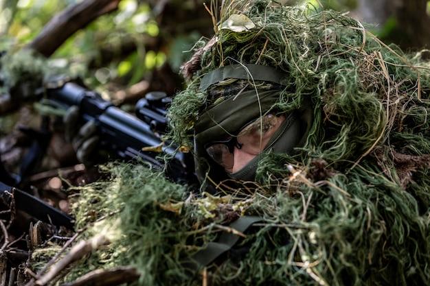 Special forces, soldaat aanvalsgeweer met geluiddemper, optisch zicht. achter dekking wachtend in hinderlaag
