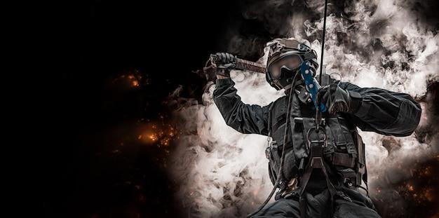 Special forces-soldaat hangt aan een touw en zwaait met een speciaal apparaat om ramen te breken. swat, politie, terrorismebestrijding concept. rook en vuur. gemengde media