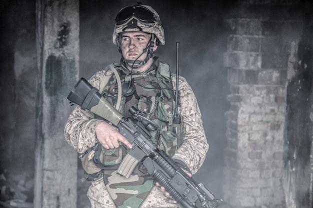Special forces soldaat, marine corps infanterist, commando-jager in helm en kogelvrije vesten, uitgeruste tactische radio, gewapend met dienstgeweer met optisch vizier en granaatwerper in rokerige ruïnes