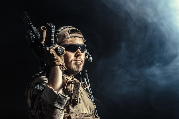 Special forces soldaat met geweer op donkere achtergrond