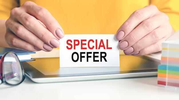 Speciale aanbieding is geschreven op een wit visitekaartje in de handen van een vrouw. bril, tablet en blok met veelkleurig papier voor notities.