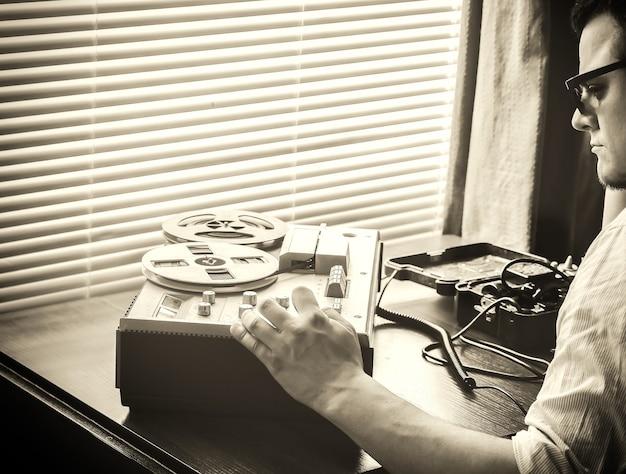 Speciale agent houdt veldtelefoon ussr vast. agent afluistert op de bandrecorder. kgb-spionagegesprekken. retrokleuren.