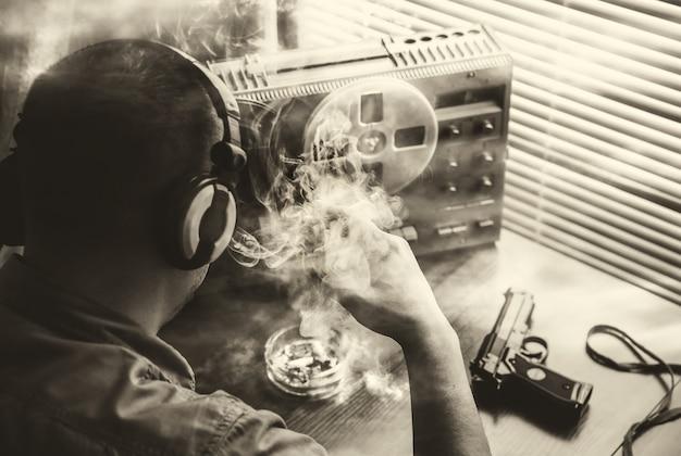 Speciale agent luistert op de bandrecorder. agent rookt een sigaret. kgb die gesprekken bespioneert. pistool op tafel.