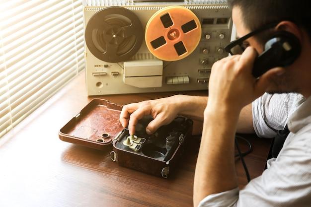 Speciale agent spreekt op veldtelefoon ussr. agent afluistert op de bandrecorder. kgb-spionagegesprekken.
