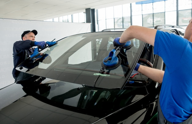 Speciale automobielarbeiders die voorruit of voorruit van een auto in de garage van het autobenzinestation vervangen.