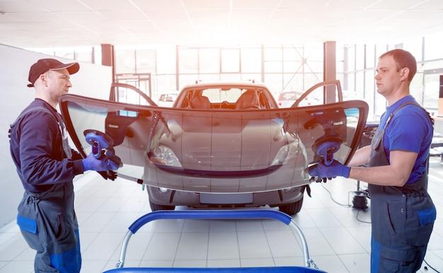 Speciale automobielarbeiders die voorruit van een auto in autodienst vervangen