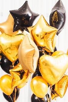 Speciale dagen decoratie. fancy party essentieel. gouden en zwarte ronde, hart, stervormige ballonnen op wit.