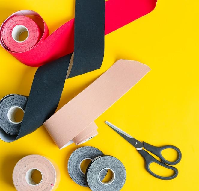 Speciale fysio-tapes rollen van verschillende kleuren en schaar voor snijden op geel. Kinesiologie tapingbehandeling.