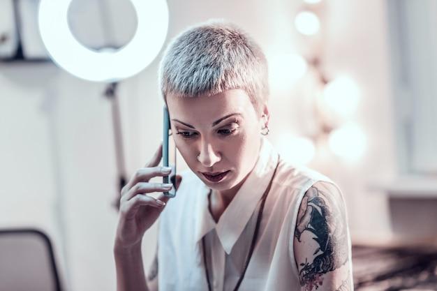 Speciale tattoo studio. verrast blonde vrouw bedekt met gekwalificeerde tatoeages praten op mobiele telefoon zittend in kantoor
