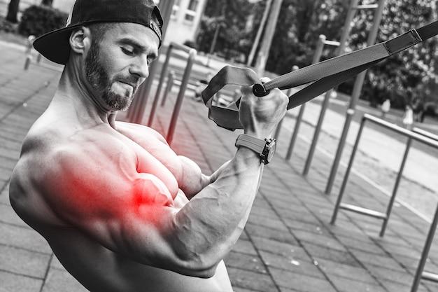 Specialisatie voor biceps. man tijdens training met ophangriemen op straat