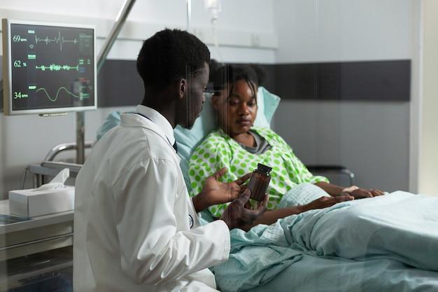 Specialist die de behandeling uitlegt aan de zieke patiënt in de ziekenhuisafdeling in de kliniek. afro-amerikaanse arts die een fles medicijnen, pillen op recept voor gezondheidszorggeneeskunde en immuniteit toont