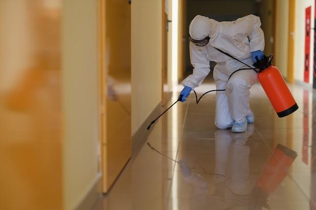 Specialist in beschermend pak en masker desinfecteert gangenclose-up