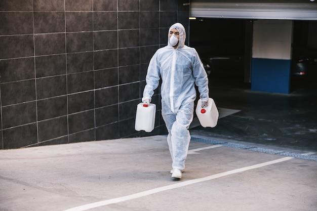 Specialist in hazmat-pakken die voorbereidingen treffen voor het reinigen en desinfecteren van covid-19-cellen-epidemie, wereldpandemisch gezondheidsrisico.