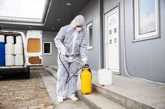 Specialist in hazmat-pakken die zich voorbereiden op het reinigen en desinfecteren van coronavirus-cellenepidemie
