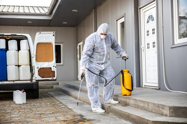 Specialist in hazmatpakken die de epidemie van coronaviruscellen reinigen en desinfecteren