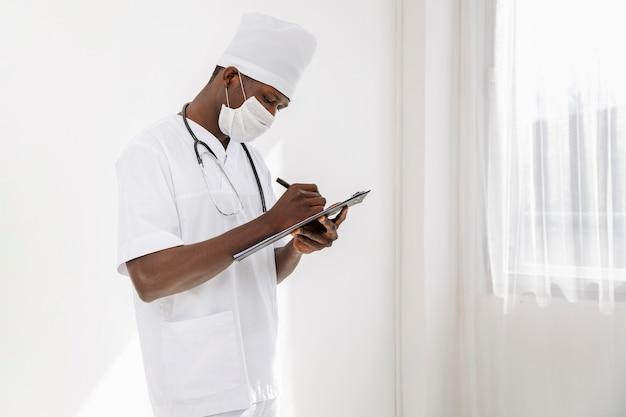 Specialist mannelijke arts die op klembord schrijft