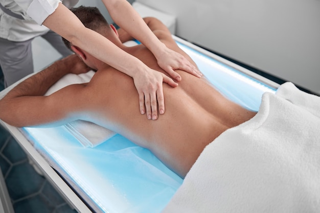 Specialist masseert de achterkant van een patiënt van middelbare leeftijd die op een gloeiende bank in de kliniek ligt