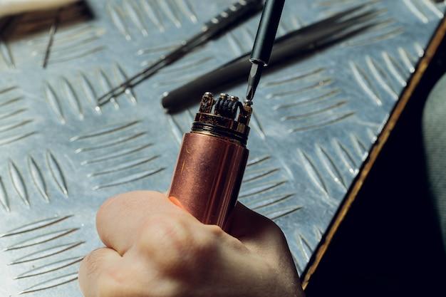 Specialist vervangt veer voor het roken van vape. professioneel onderhoud van elektronische sigaret in winkel