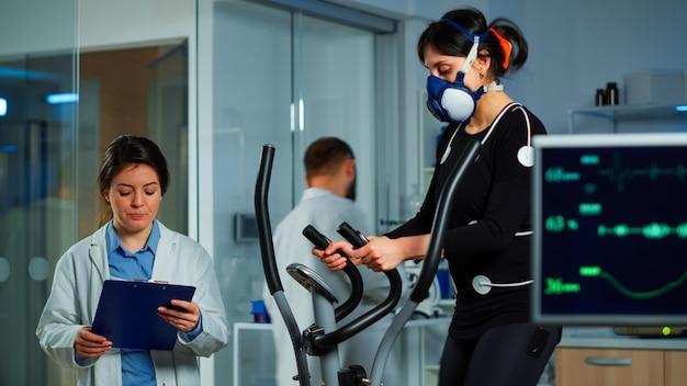 Specialisten die toezicht houden op oefeningen van de patiënt, gezondheidsinformatie op het klembord lezen, prestatieatleet die op een crosstrainer loopt die hartslag, fysiek uithoudingsvermogen, psychologische weerstand meet