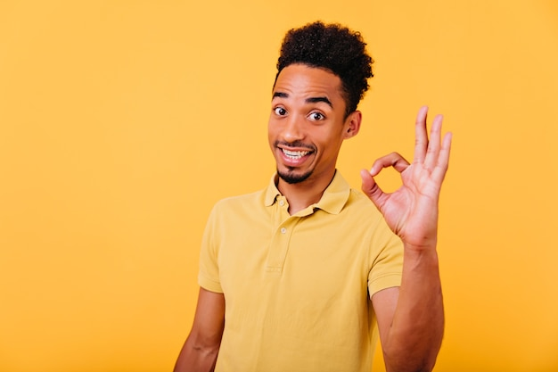 Spectaculair afrikaans model met trendy kapsel poseren met goed teken. indoor foto van verbaasd brunette zwarte man in zomer t-shirt.