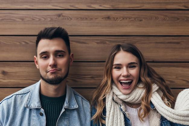 Spectaculair meisje in herfst outfit genieten van fotoshoot met vriendje. binnenfoto van twee vrienden die met glimlach op houten muur stellen.