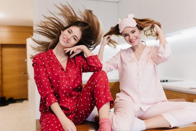 Spectaculair meisje in rode pyjama zwaaien hoofd tijdens fotoshoot thuis. binnenportret van knappe dames die in de keuken voor de gek houden.