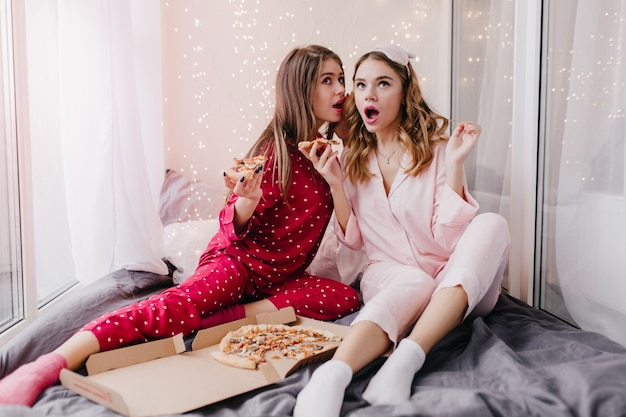 Spectaculair meisje in rood nachtpak dat geruchten deelt met beste vriend en pizza eet. vrolijke vrouwelijke modellen in pyjama's zittend op bed.
