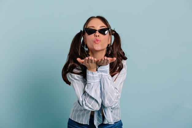 Spectaculair mooi meisje met een zwarte zonnebril en een blauw shirt stuurt een kus naar de camera die zich voordeed over geïsoleerde muur