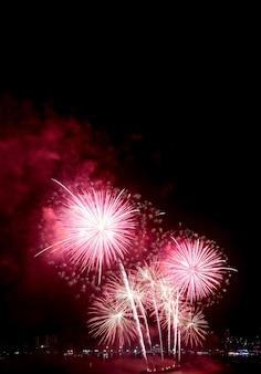 Spectaculair roze en rood vuurwerk dat in de nachtelijke hemel spettert