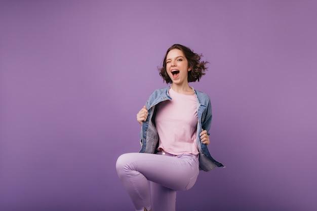 Spectaculair slank meisje in paarse broek springen met een glimlach. aantrekkelijk vrouwelijk model dat geluk uitdrukt.