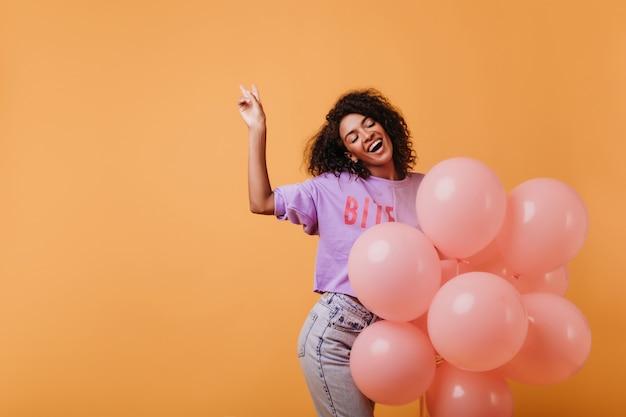 Spectaculair zwart vrouwelijk model lachend met gesloten ogen op feestje. leuk afrikaans krullend meisje dat van haar verjaardag geniet.