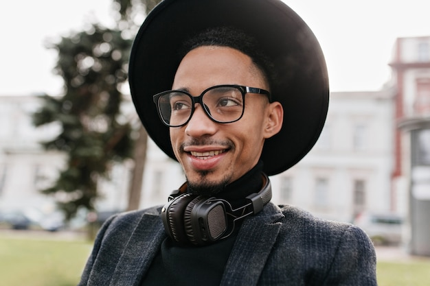 Spectaculaire afrikaanse man met oprechte glimlach poseren. buitenfoto van schattig zwart mannelijk model in glazen en koptelefoon.
