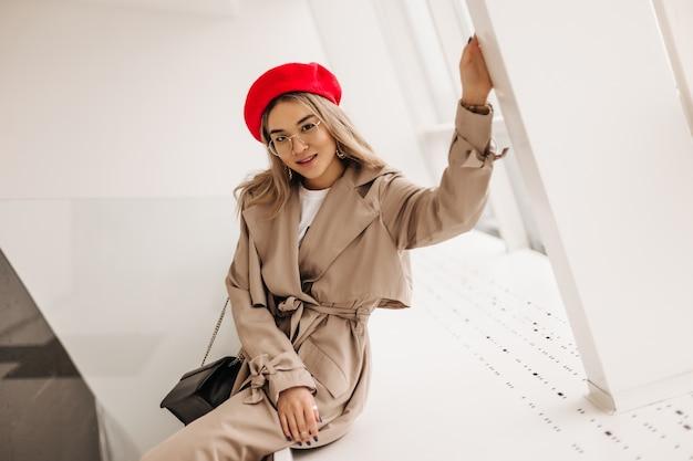 Spectaculaire aziatische vrouw met blond golvend haar gekleed in beige trenchcoat zit op een witte vensterbank in de buurt van groot raam