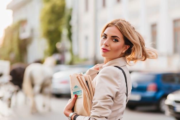 Spectaculaire blonde vrouw met haar zwaaien opknoping uit alleen krant naar huis