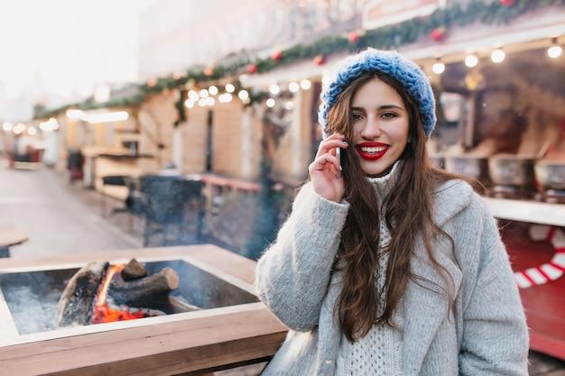 Spectaculaire brunette vrouw in wollen grijze jas poseren op kerstmarkt met glimlach. romantisch meisje met lang kapsel draagt blauwe hoed staande op straat ingericht voor wintervakantie.