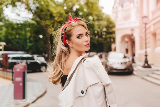 Spectaculaire dame met blond haar kijkt achterom terwijl ze jas op schouder draagt