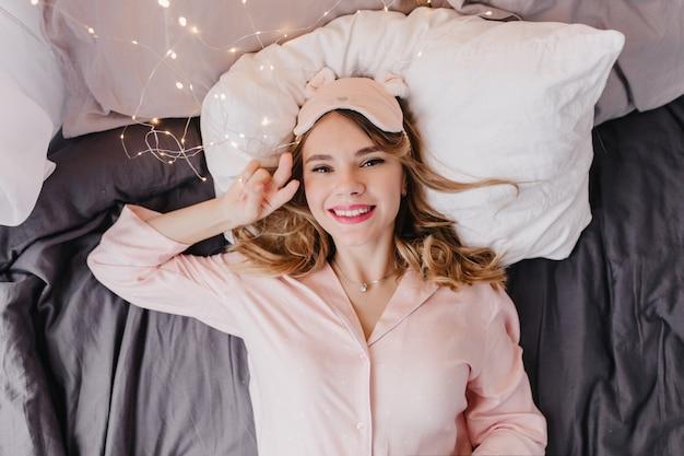 Spectaculaire europese vrouw die in de ochtend in bed ligt.